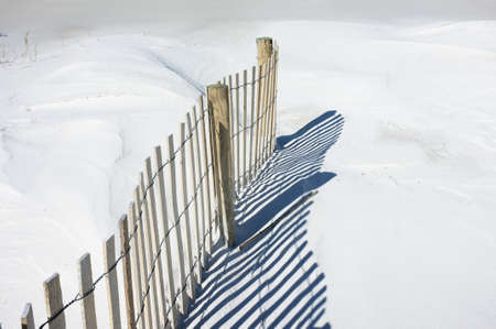 pensacola: Sand fence and shadows on snowy white dunes at the beach.