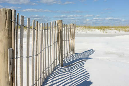 Beautiful day at the beach with white sand, sand fence and sea oats against a blue sky.