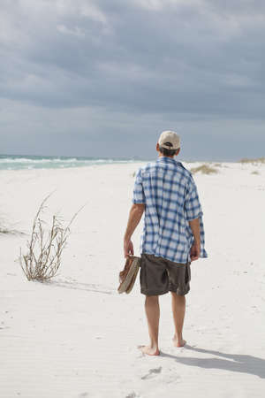 gazing: Man walking on a white sandy beach Stock Photo