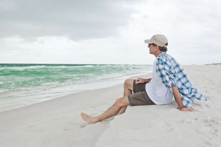 gazing: Man sitting on a white sandy beach, gazing out to sea