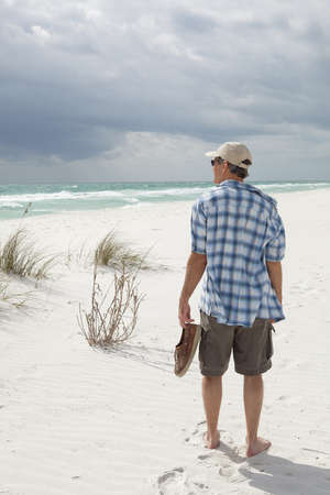 gazing: Man stopping to gaze out to sea on a white sandy beach Stock Photo