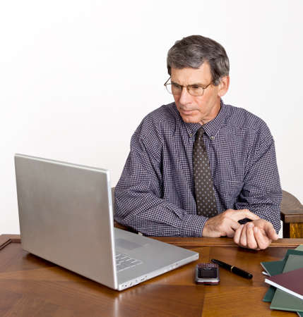 Worried businessman at desk and computer checking his own pulse.