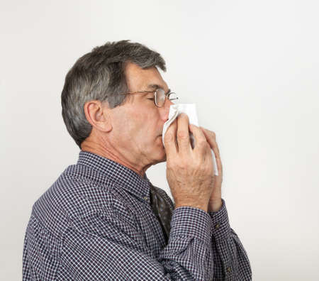 communicable: Man with bad cold or flu sneezing into handkerchief.  Stock Photo