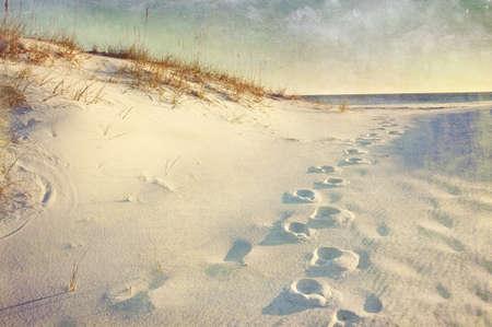 Voetstappen in het zand duinen die naar de oceaan bij zonsondergang. Zachte artistieke behandeling met canvas textuur, graan en penseelstreken toegevoegd voor effect.