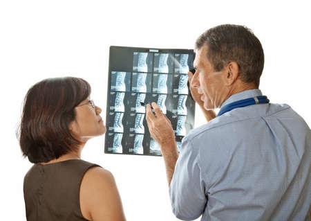 Mannelijke arts en vrouwelijke patiënt het bekijken en bespreken van MRI (Xray) Spinal Scans Stockfoto