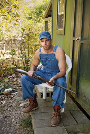hillbilly: Handsome but threatening-looking man sitting in a plastic chair under a magnolia tree holding the old family shotgun  Stock Photo
