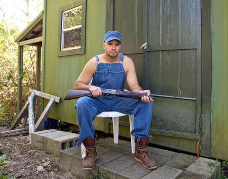 salopette: Angry homme qui cherche jeune en salopette vieux, assis et tenant un fusil de chasse en dehors d'une cabine ou d'un camp de chasse.