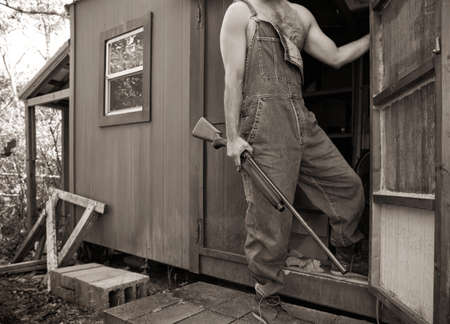 shack: Sepia photo of shirtless man in overalls holding a shotgun guarding his backwoods camp or shack  Man is shown from the neck down  Stock Photo