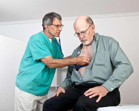 Mannelijke arts luistert naar het hart oudere man met stethoscoop Stockfoto