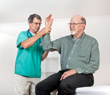 Male doctor, surgeon or nurse examines a senior man's arm. Patient is in obvious discomfort, wincing in pain.