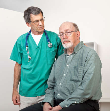 Male Doctor or Nurse Listening to  and Comforting Depressed Senior Male Patient