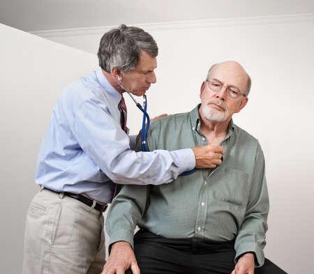 男性の医師が聴診器でそれ以上の年齢の人間の心に聞く