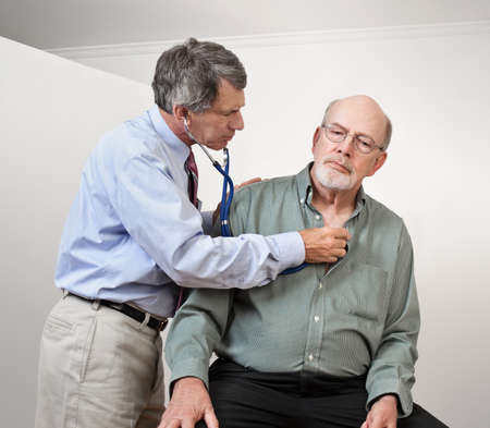 Male doctor listening to older mans heart with stethoscope photo