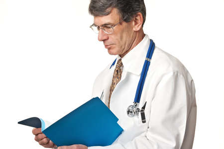 Doctor in closeup view reading a patients file in a folder. Stock Photo