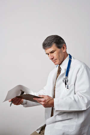 Handsome mature male doctor reviewing his notes with clipboard and pen. Plain gray background.  Stock Photo