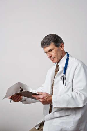 Knappe volwassen mannelijke arts beoordelen zijn aantekeningen met klembord en pen. Plain grijze achtergrond.
