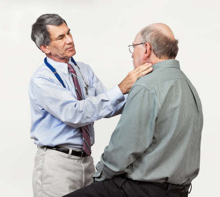 Mature male doctor examining senior male patien't neck for swollen glands. Plain neutral background. photo