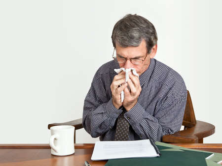 Businessman at desk blowing nose.