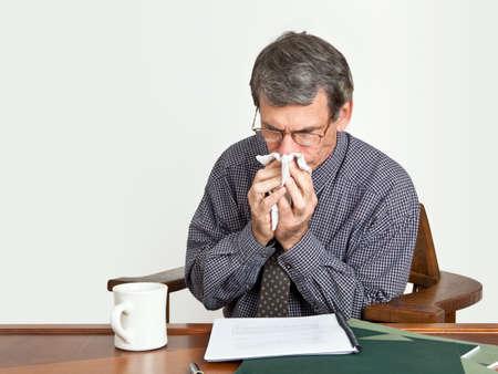 sinusitis: Businessman at desk blowing nose.