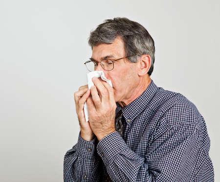 Man met een zware verkoudheid of griep niezen in de zakdoek. Neutraal grijze achtergrond. Stockfoto