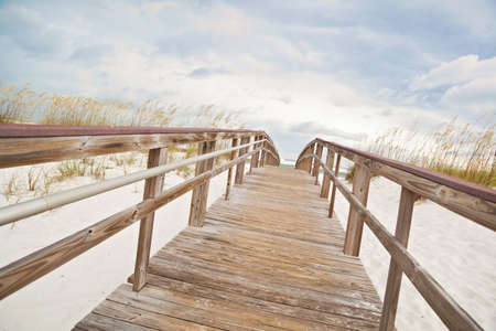 Wooden boardwalk at the beach through the dunes to the surf and ocean. photo