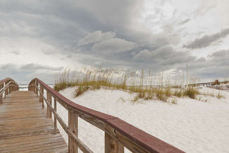 Wooden boardwalk footpath through the sand dunes to the ocean and beach at Gulf Islands National Seashore in Florida.