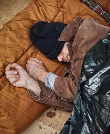 wino: Closeup of unshaven homeless man sleeping in the street with sleeping bag, tarpaulin, cardboard underneath him  Stock Photo