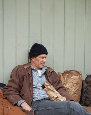 hobo: Older homeless man sleeping in a seated posture, leaning on a metal wall, surrounded by his pack, sleeping bag, wine bottle in a paper bag, etc