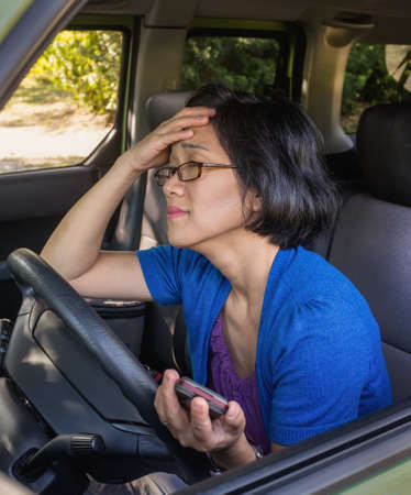 Frustrated unhappy woman in her car in a traffic jam  photo
