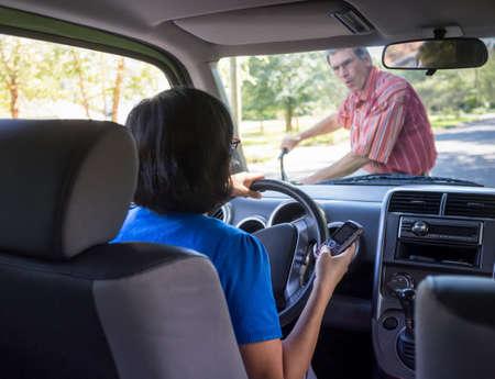 Vrouw rijden en texting op mobiele telefoon, op het punt om een fietser raken Stockfoto