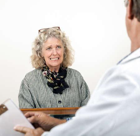 Bezorgd bange volwassen vrouw overlegt met haar arts in zijn kantoor Focus ligt op het gezicht van de vrouw