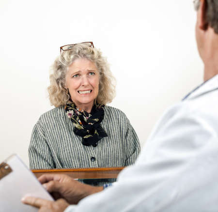 sad old woman: Worried frightened mature woman consults with her doctor in his office  Focus is on the woman's face   Stock Photo