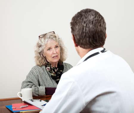 Mooie rijpe vrouw overlegt met haar arts in zijn kantoor Focus ligt op het gezicht van de vrouw