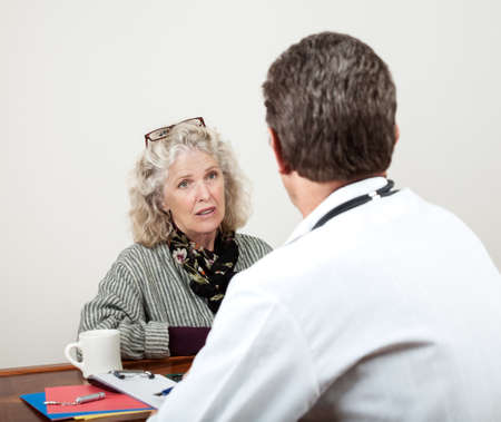 consultation woman: Pretty mature woman consults with her doctor in his office  Focus is on the woman's face