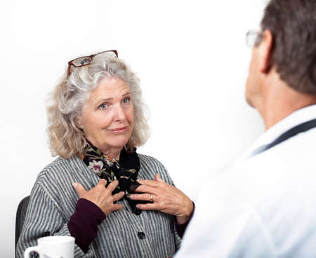 distressed: Pretty mature woman consults with her doctor in his office  Focus is on the woman's face  Patient is levelling with the doctor  Stock Photo