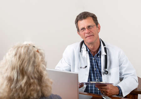 Friendly attentive doctor listens to female patient in his office. photo
