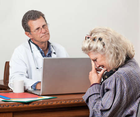 impatient: Pretty mature woman consults with her doctor in his office. Focus is on the woman's face. She looks worried and tearful. The doctor looks bored and impatient.