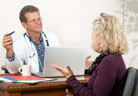 Friendly attentive doctor listens to female patient in his office. Focus is on the female patient.