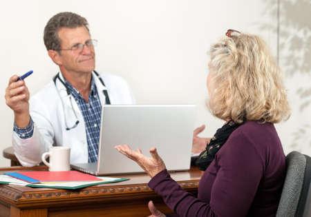 Vriendelijke attente arts luistert naar vrouwelijke patiënt in zijn kantoor. Focus ligt op de vrouwelijke patiënt. Stockfoto