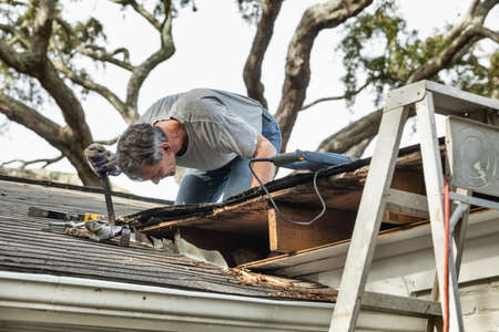 damaged roof: Man using crowbar to remove rotten wood from leaking roof  After removing fascia boards he has discovered that the leak has extended into the beams and decking  Stock Photo