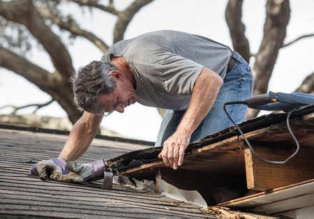 lekken: Close-up van man met behulp van koevoet en zag tot rot hout uit lekkende dakbedekking verwijderen Na het verwijderen van boeiboorden hij heeft ontdekt dat het lek heeft uitgebreid in de balken en terrasplanken