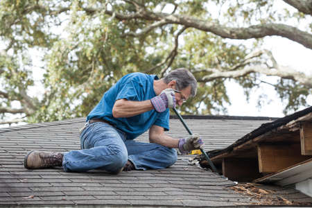 Man using crowbar to remove rotten wood from leaky roof  After removing fascia boards he has discovered that the leak has extended into the beams and decking  photo