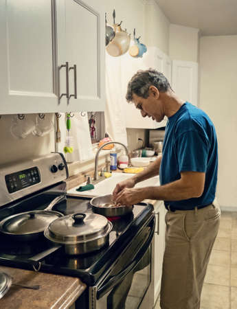 Candid lifestyle shot of a mature man cooking dinner alone in a plain small kitchen. Man is backlit, high speed shot with wide aperture, some grain evident. Stock Photo - 17035138