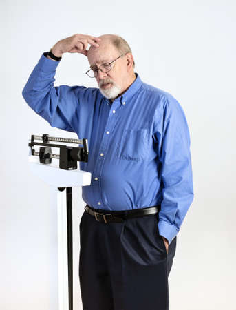 Senior caucasian man weighing himself on vertical weight scale, while scratching his head in confusion Stock Photo - 17566892