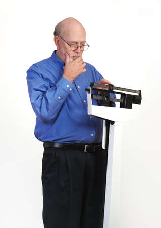 Senior caucasian man weighing himself on vertical weight scale. He looks thoughtful and concerned. Stock Photo - 17560566