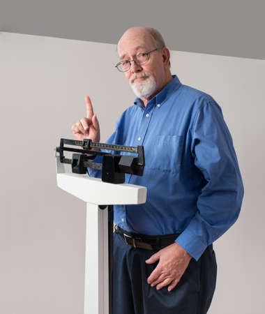 Senior caucasian man weighing himself on vertical weight scale. He looks pleased and confident.. Stock Photo - 17566895