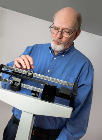 Senior caucasian man weighing himself on vertical weight scale. Closeup view. photo
