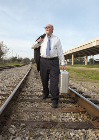 A senior businessman in suit and tie carrying his old suitcase, walks down a railroad track, tired, defeated, and jobless with no prospects. Nearby interstate overpass adds further symbolism as he is on an outmoded railroad track, life has passed him by. photo