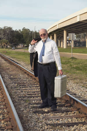 travelling salesman: A senior businessman in suit and tie carrying his old suitcase, walks down a railroad track, tired, defeated, and jobless with no prospects. Nearby interstate overpass adds further symbolism as he is on an outmoded railroad track, life having passed him b Stock Photo