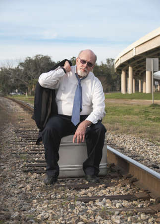 Jobless senior businessman sits on suitcase on railroad train tracks pondering his uncertain future.